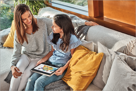 A mother and her daughter sit on a couch as the daughter uses Paint 3D on a laptop