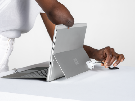 A woman uses the adaptive kit opener with a lanyard to open the Surface Pro kickstand.
