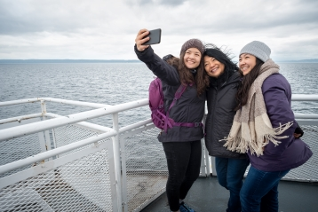 A family taking a selfie on a ferry