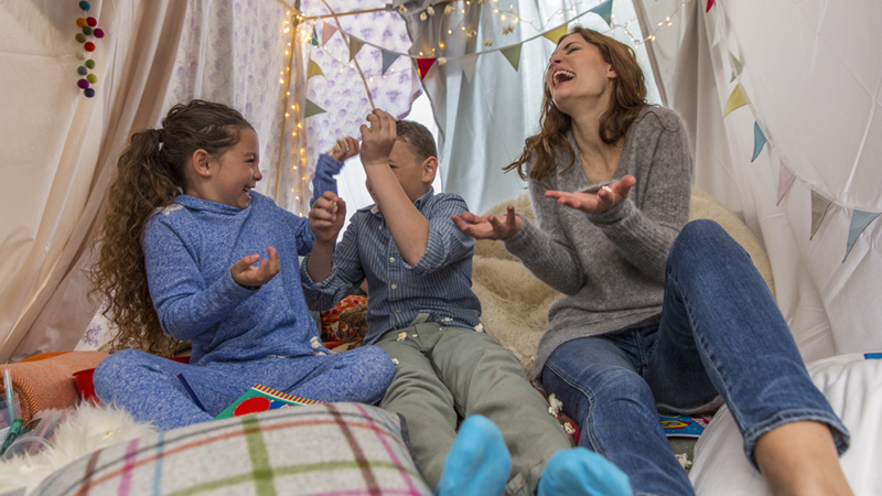 A mother and her two young children sit together in an indoor tent under string lights, laughing