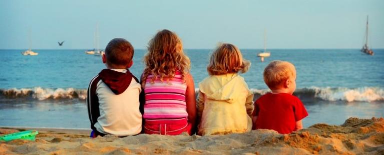 photo of 4 kids sitting on a beach