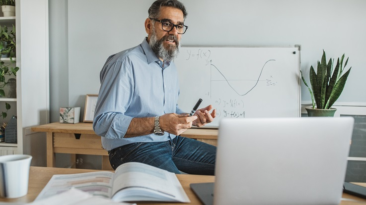 Photo of a teacher at a whiteboard with a laptop.