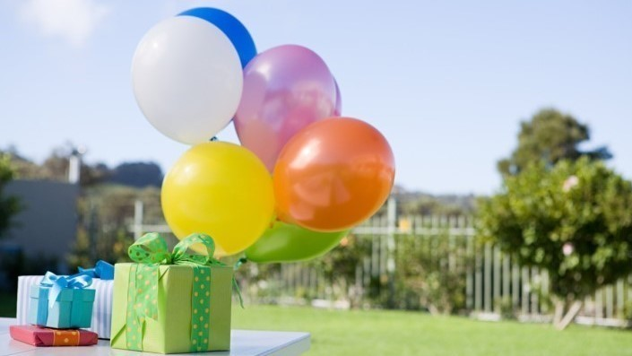 photo of a wrapped present and balloons