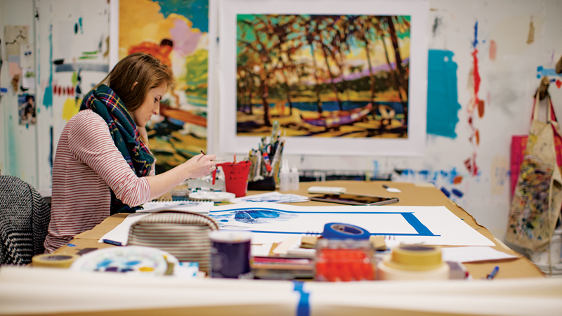 A white woman sits at a table in an art studio, painting