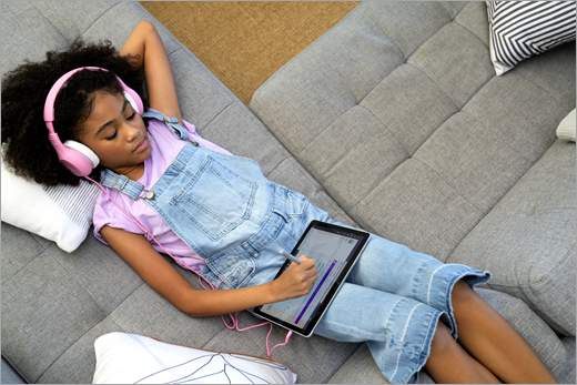 A Black female student learns from home while wearing headphones and laying on a couch as she uses OneNote, writing with a digital pen.