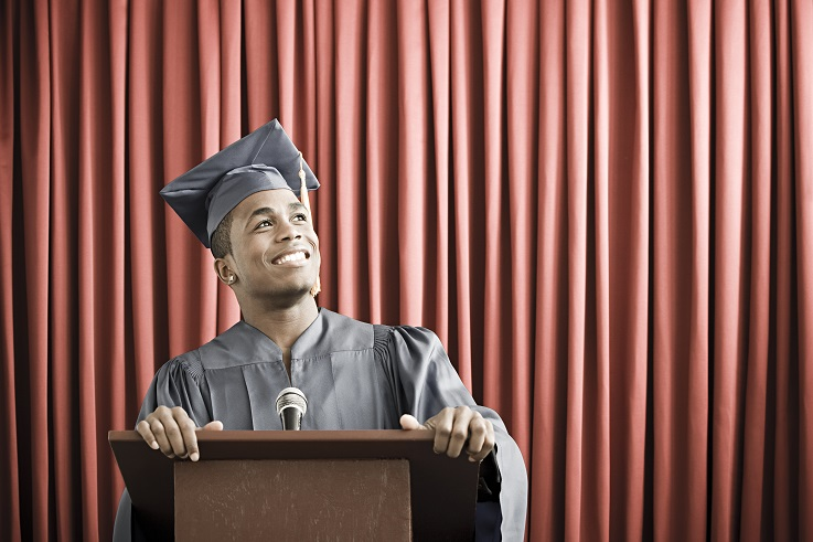 Photo of a young man wearing a graduation robe and standing at a podium.