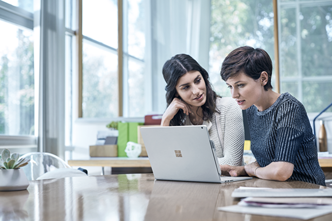 Two women collaborating on a laptop