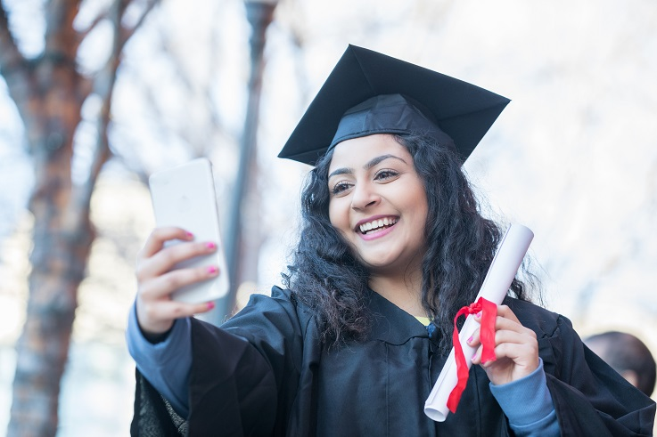 Photo of a person in cap and gopwn taking a graduation selfie.