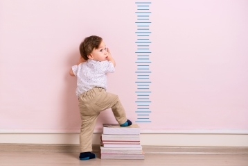 A young child next to a growth chart
