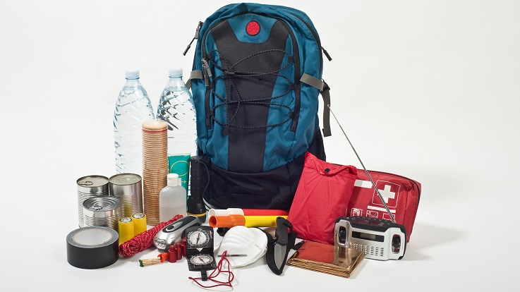 Photo of a backpack, first aid kit, radio, water, and other emergency supplies.