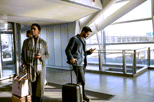People at an airport checking their wireless devices.
