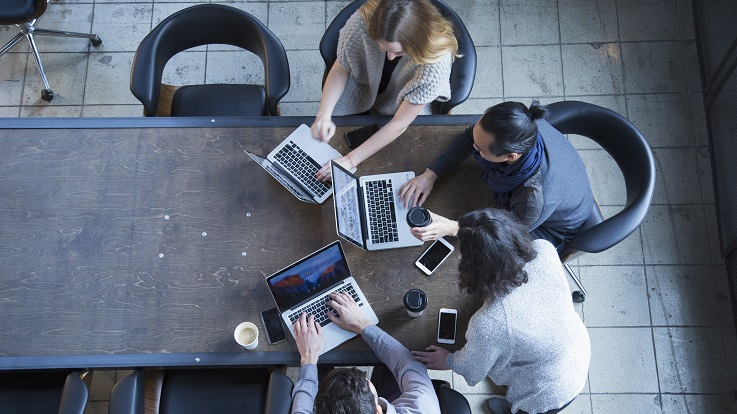 overhead photo of four people working on computers and devices at a table
