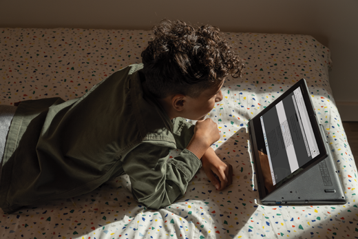 A middle school boy reads a webpage with Immersive Reader in Microsoft Edge.