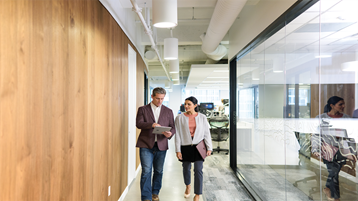 Female and male coworkers walking down office hallway in conversation.