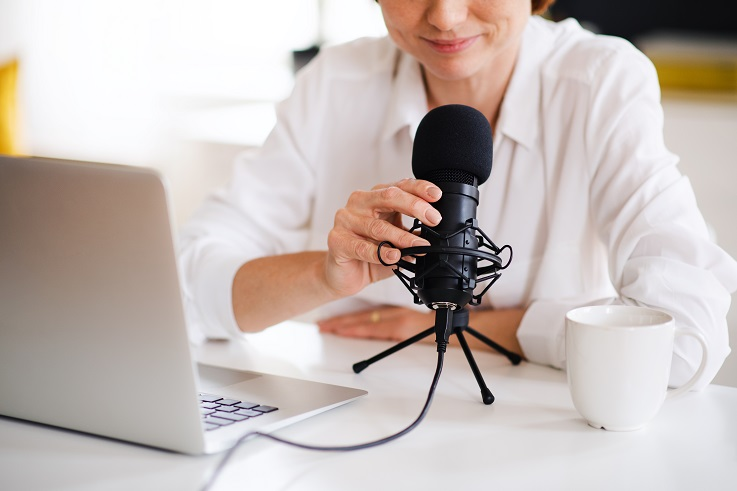 Photo of a person with a laptop speaking into a microphone.