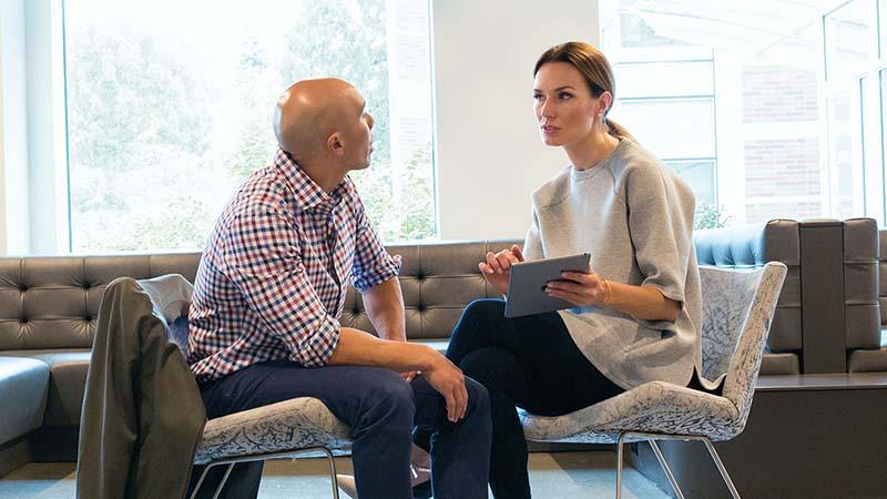 Un hombre y una mujer hablando en una oficina
