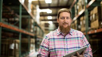 Un empleado en un almacén que sujeta una tableta