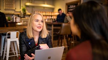 2 mujeres conversando en una cafetería