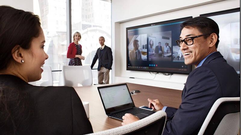 Usuarios que se reúnen físicamente y a través de Skype en una sala de conferencias