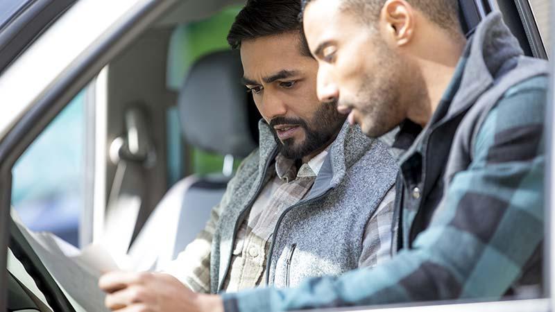 Dos hombres mirando algo de papeleo, un Mane está sentado en el asiento de los conductores de un camión, el otro lado de él