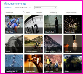 Captura de pantalla de una biblioteca de activos en SharePoint. Muestra imágenes en miniatura de varios vídeos e imágenes que contiene la biblioteca. También muestra las columnas de metadatos estándar para los activos multimedia.