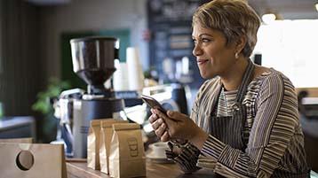 Un camarero mira su teléfono en una cafetería