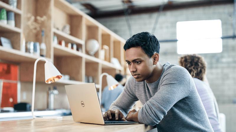 Valokuva opiskelijasta kannettavan tietokoneen kanssa