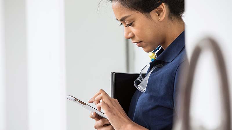 Nainen tarkistamassa tietoja puhelimestaan