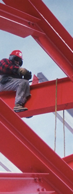 Rakennustyöläinen istumassa palkilla