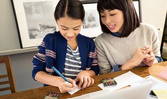 Äiti ja tytär tekemässä kotitehtäviä