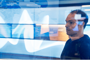 Kuva miehestä tietoturvakeskuksessa valvomassa kyberhyökkäyksiä.