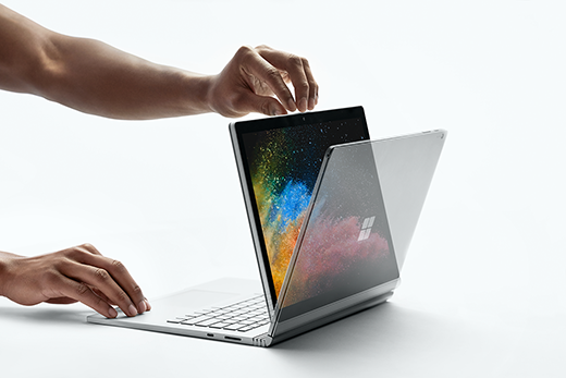 Kuva käsistä avaamassa Surface Book 2:ta samalla, kun laite on katselunäkymässä.