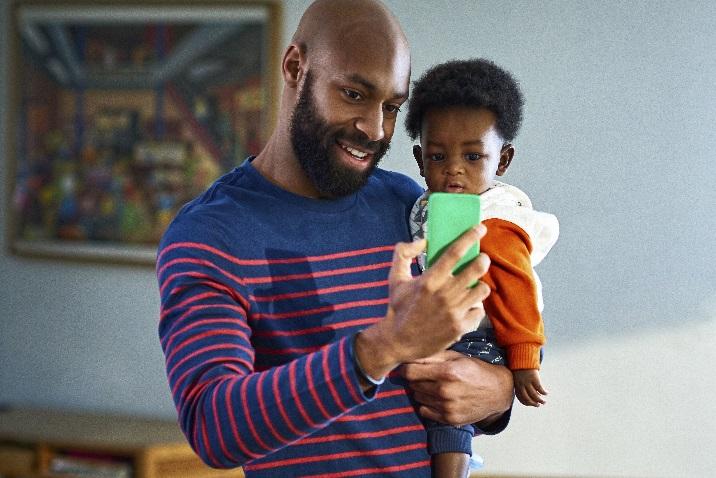 Kuva miehestä, jolla on pieni lapsi ja joka puhui puhelimessa