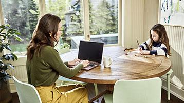 Nainen työskentelemässä kannettavalla tietokoneella tytön kanssa, joka piirtää tai kirjoittaa pöydän ääressä