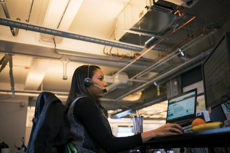 Nainen istuu tietokoneen ylle kuulokkeet päässä