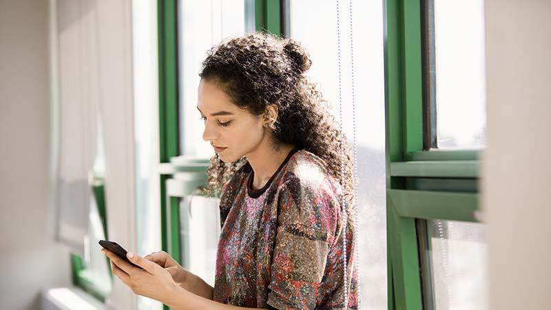 Une femme debout par une fenêtre travaillant sur un téléphone