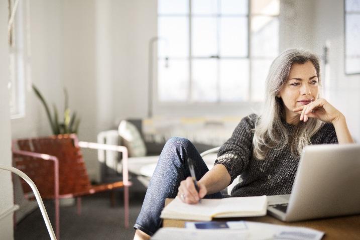 Photo d'une femme regardant un ordinateur portable tout en prenant des notes sur son agenda.