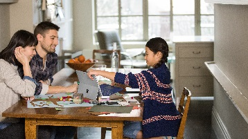 Image d'une famille autour d'une table de cuisine et travaillant sur un ordinateur