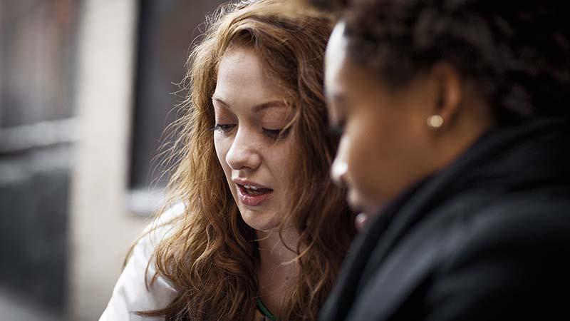 שתי נשים מדברות ומסתכלות על משהו עבור פרוייקט