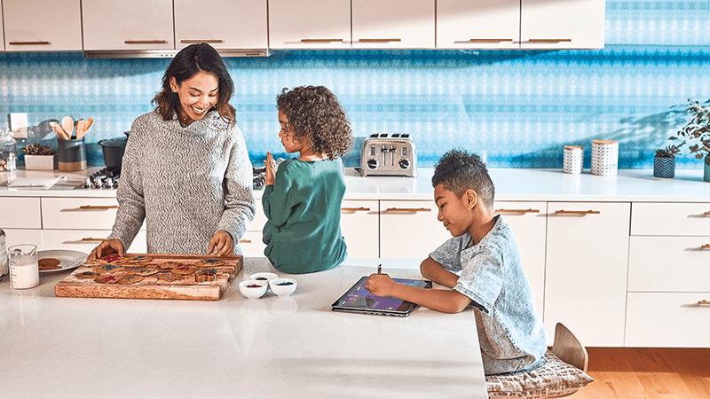 אישה עומדת ושני ילדים יושבים יחד במטבח.