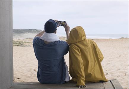 זוג מצלם תמונה על החוף