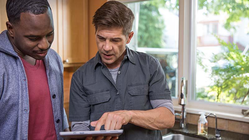 שני אנשים במטבח מסתכלים על טבליה