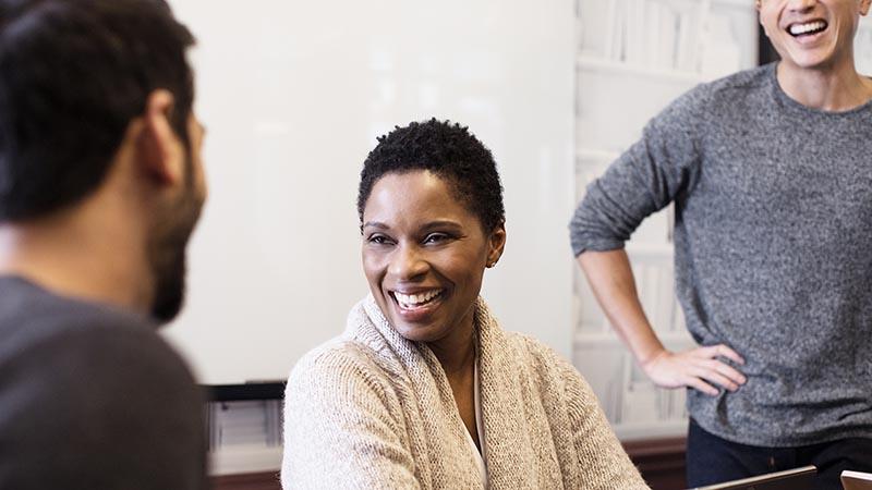 אישה ושני גברים מחייכים ומדברים במשרד