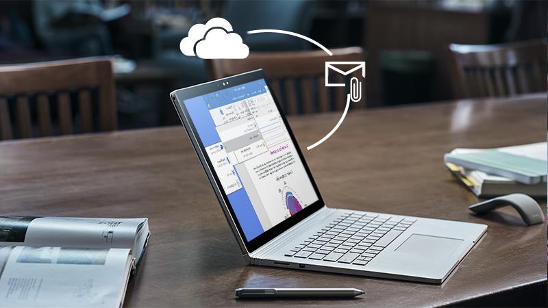 תמונה של מחשב נישא על שולחן עם קובץ מצורף וסימנים של OneDrive