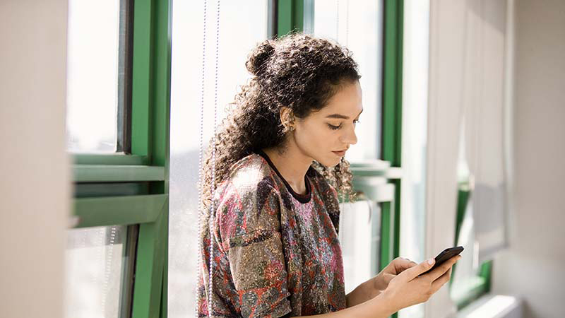 אישה שעומדת ליד חלון עובד בטלפון