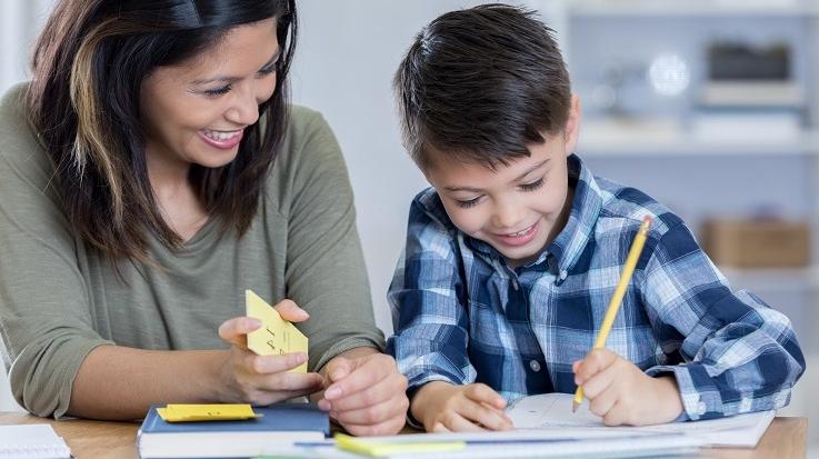 תמונה של מבוגר שעוזר לילד עם שיעורי בית.