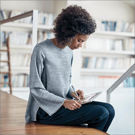 צילום של אישה עובדת במחשב Tablet מסוג Surface.