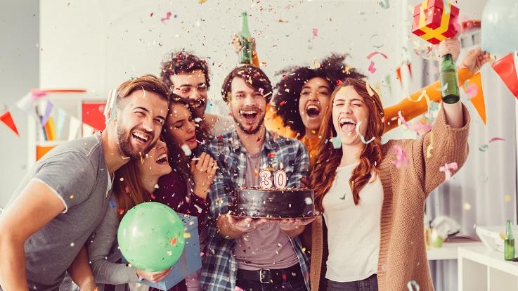 תמונה של קבוצה של חברים חוגגים עם אוכל, משקאות ו- confetti.