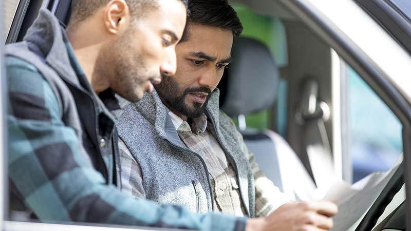 שני גברים מסתכלים על ניירת-אחת מאנה יושבת במושב של נהגי משאית, והשני עומד לידו