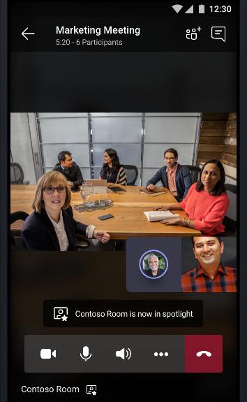 תמונה של פגישה מקוונת של צוותים עם חדר ישיבות מלא אנשים שמדברים עם שני משתתפים אחרים בפגישה.